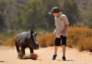 Hunter Mitchell from Cape Town with rhino orphan Osita at Aquila Private Game Reserve. Hunter raises funds to fight rhino poaching.